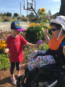A young girl hands a young boy with disabilities some flowers