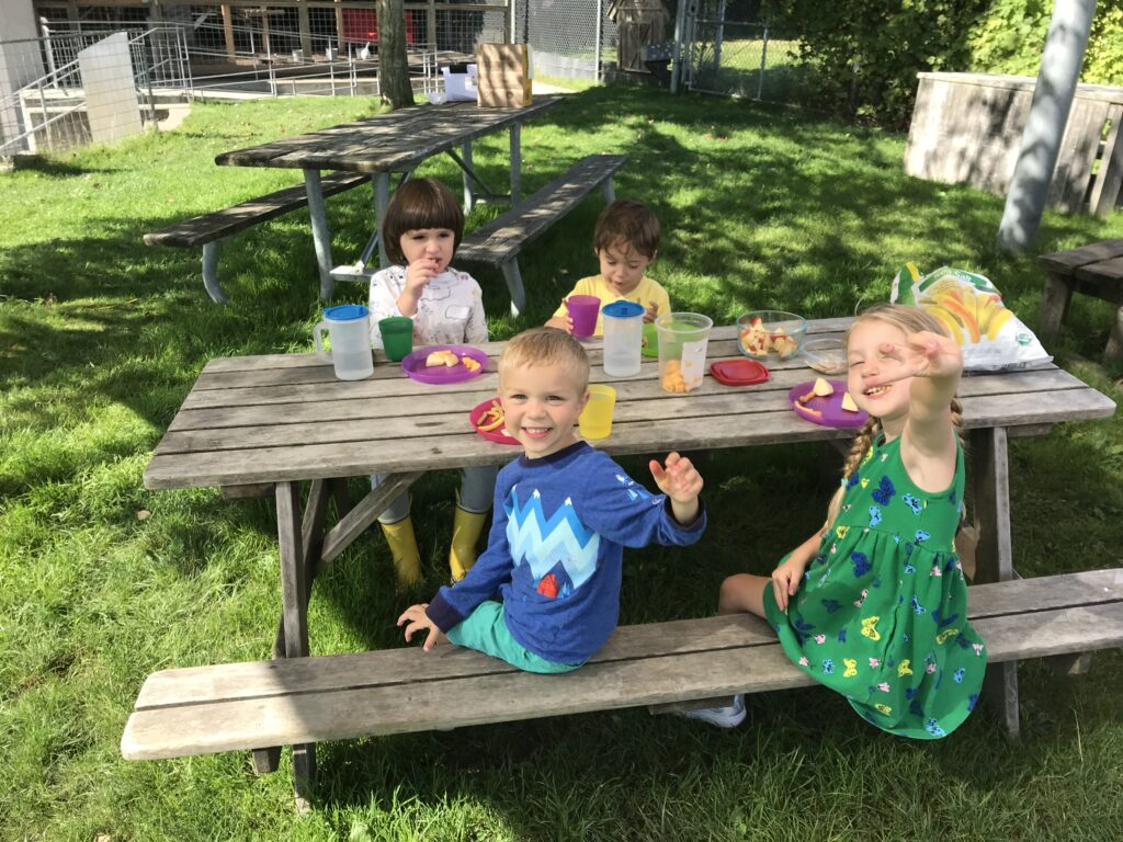 Four children eat snack together at an outdoor picnic table