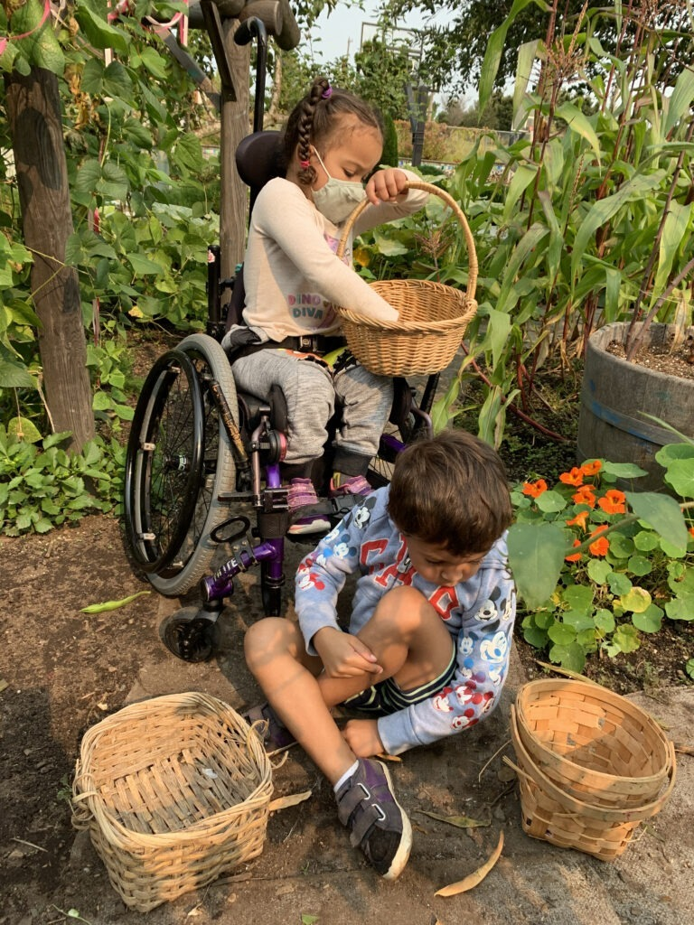 Two preschoolers garden together. One is sitting in her wheelchair, one is on the ground.