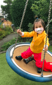 A child plays on the swing at the PlayGarden wearing a mask