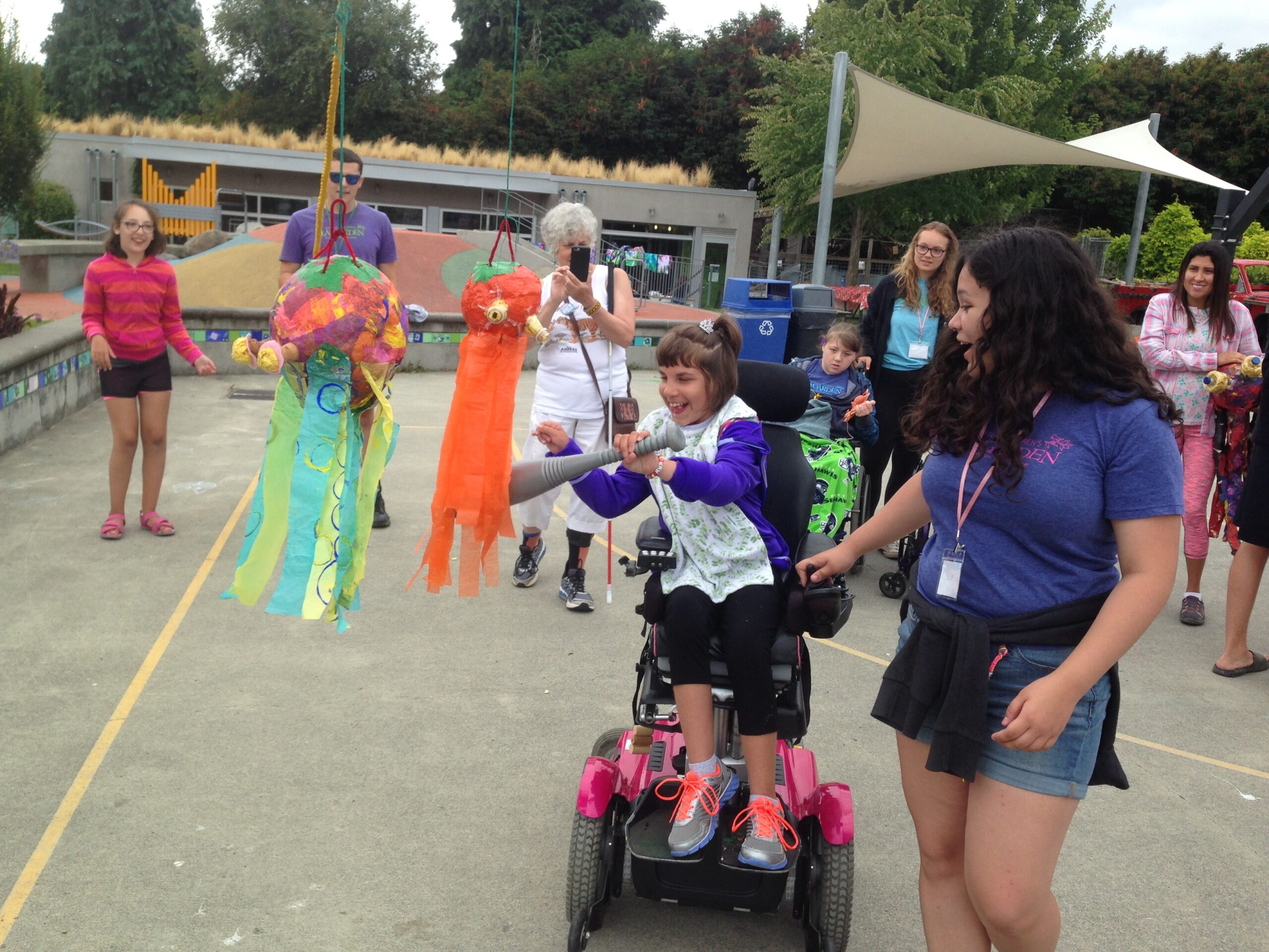 A teen sitting in her power wheelchair hits a pinata with the help of a camp counselor. The other teens cheer her on in the background.