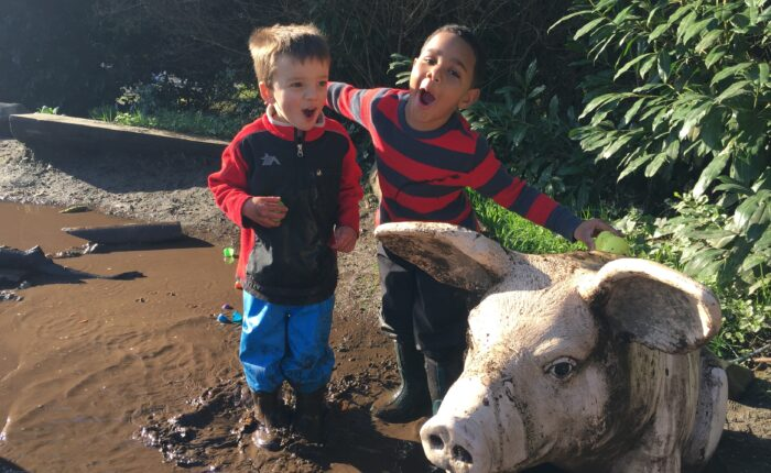 Two children play in the mud with the PlayGarden pig, Wilbur.