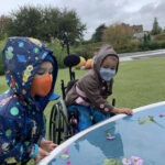 Kids wearing masks and playing in the rain at the PlayGarden