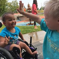 Two kids give each other a high five at summer camp